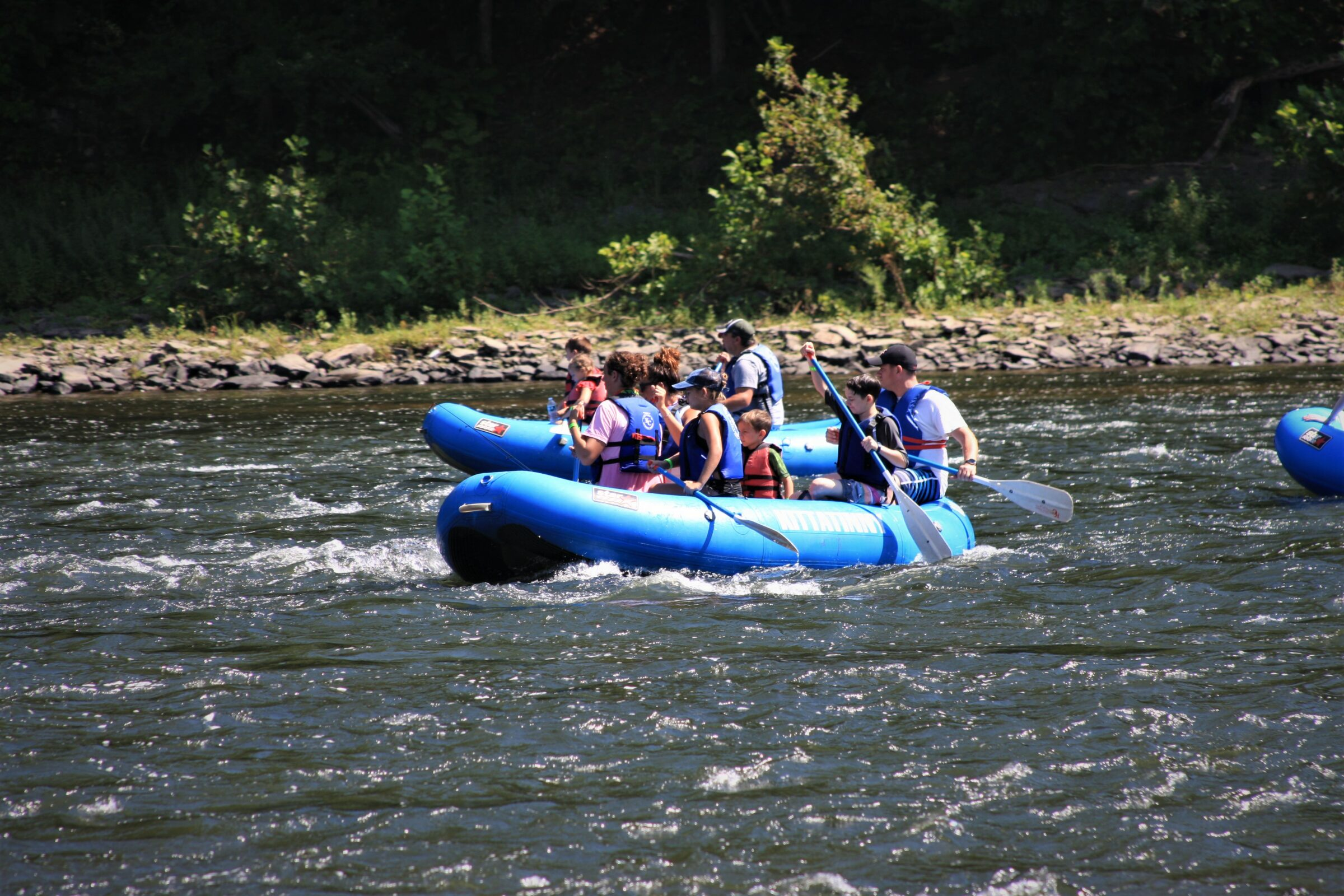 Boaters enjoying a rafting trip while wearing their life jackets.