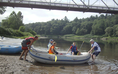 family of five guiding the raft into the river