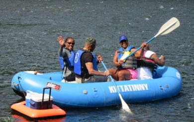 family of four in raft with a cooler raft in tow