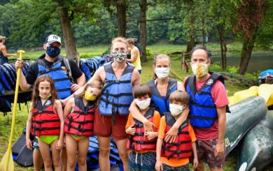 family in life jackets ready for rafting trip