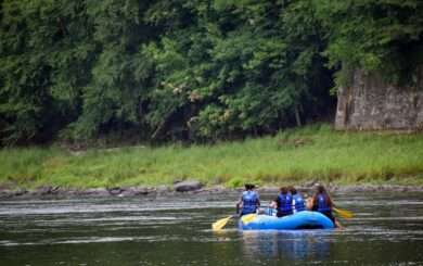 rafters in raft drifting down river