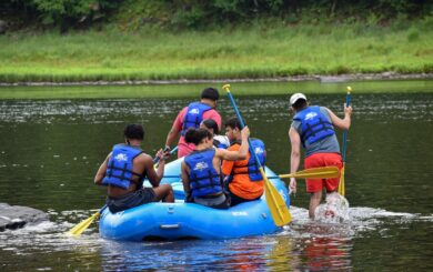 rafters pushing raft into river