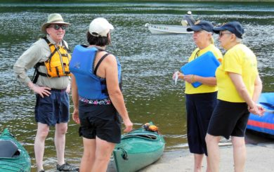 a group of kayakers discussing the conditions of the River
