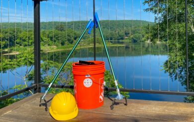 a bright orange bucket and yellow hard hat sit with the delaware river in the background